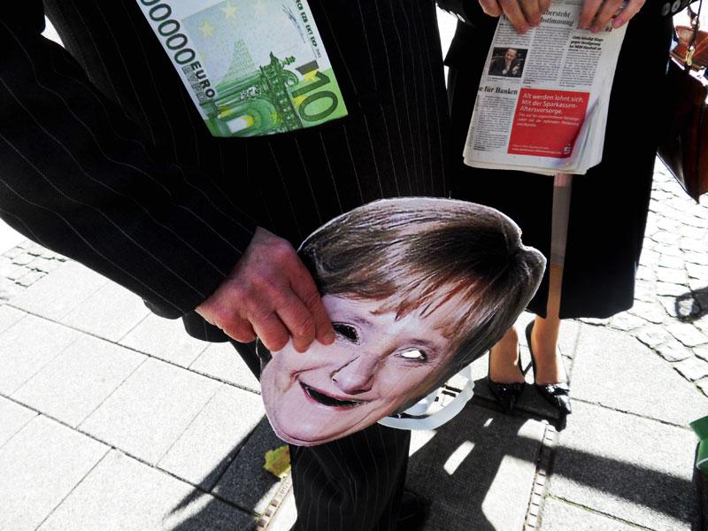 Bild: Merkel Maske Geld Anzug Banken Presse
